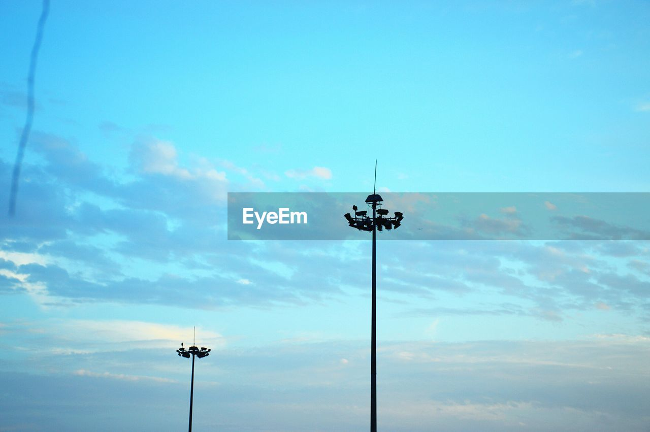low angle view, sky, blue, cloud - sky, floodlight, no people, silhouette, technology, outdoors, nature, day, electricity, beauty in nature