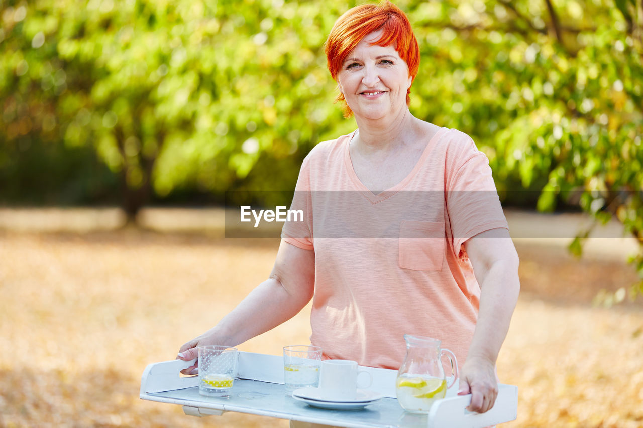 Portrait Of Redhead Woman Holding Tray While Standing Against Trees
