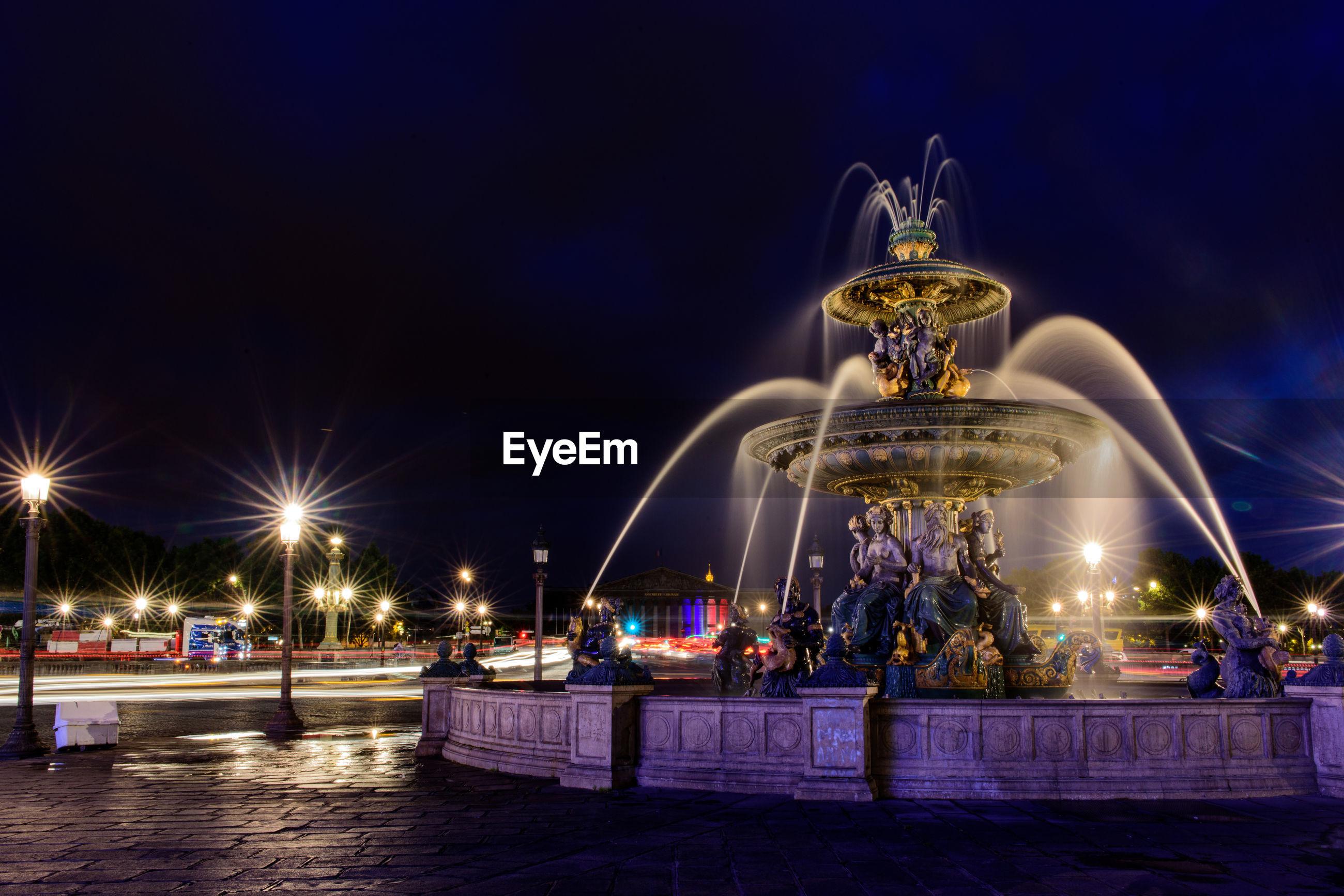 Illuminated fountain against blue sky at night