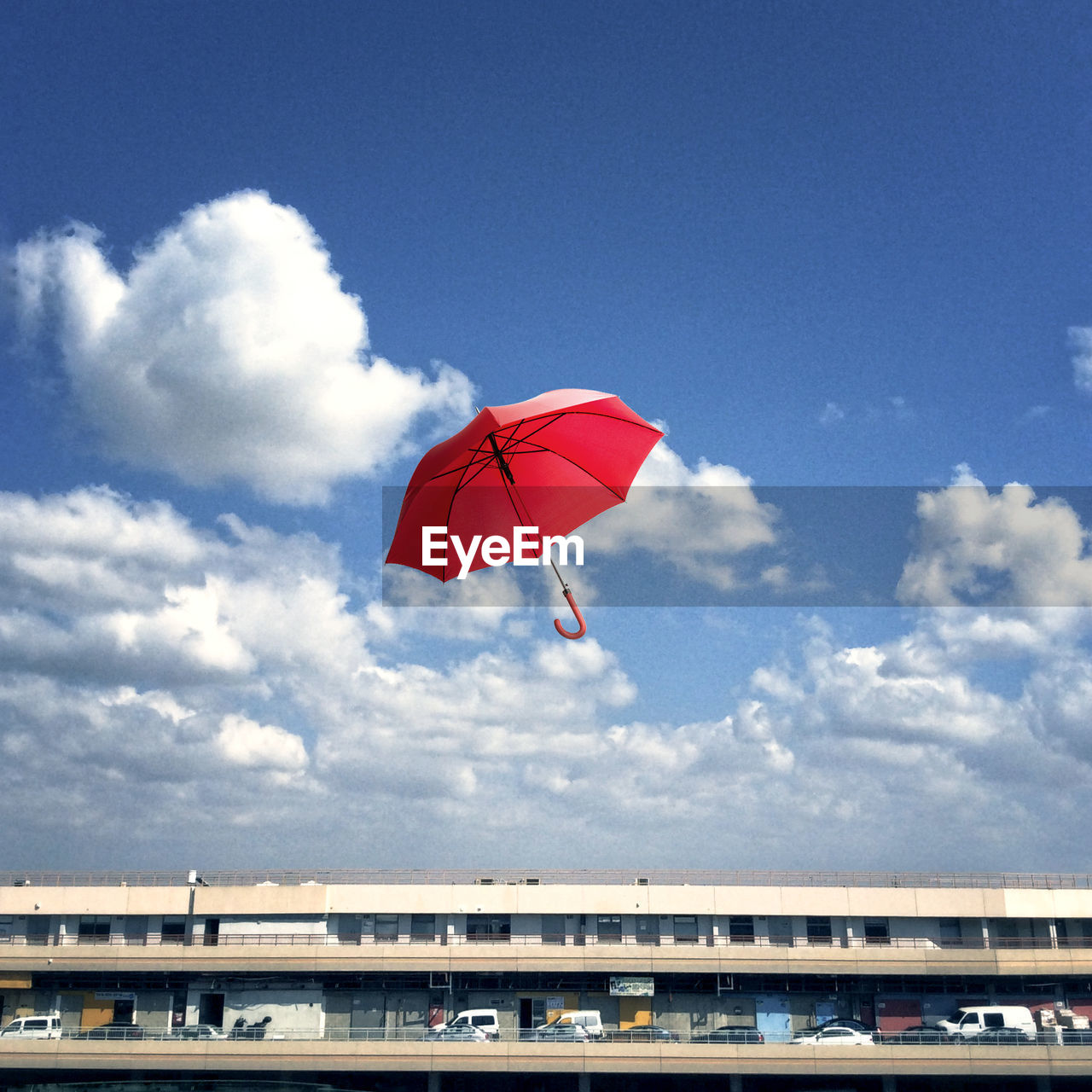 Low angle view of red umbrella in mid-air against sky
