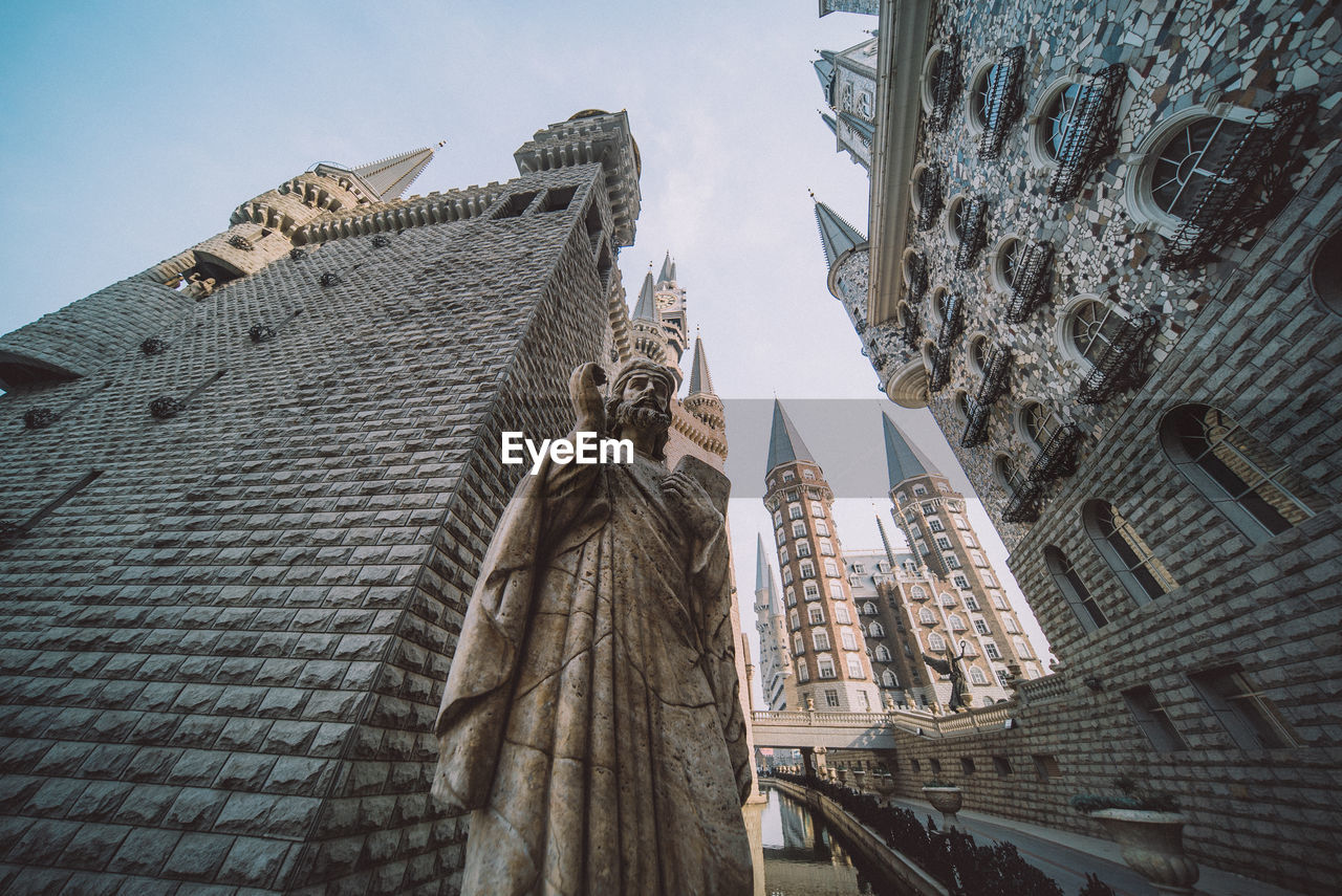 Low angle view of statue and buildings against sky in city