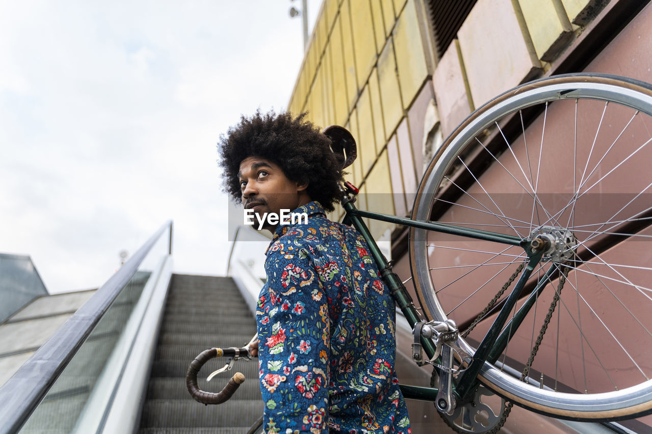 LOW ANGLE VIEW OF WOMAN LOOKING AT BICYCLE AGAINST SKY