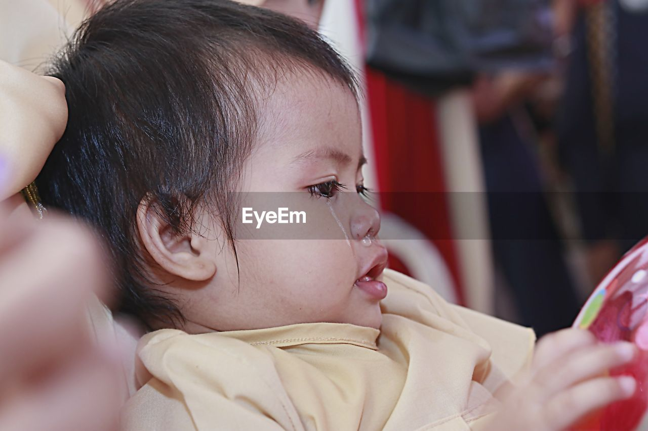 Close-up of cute baby girl with runny nose and tears looking away