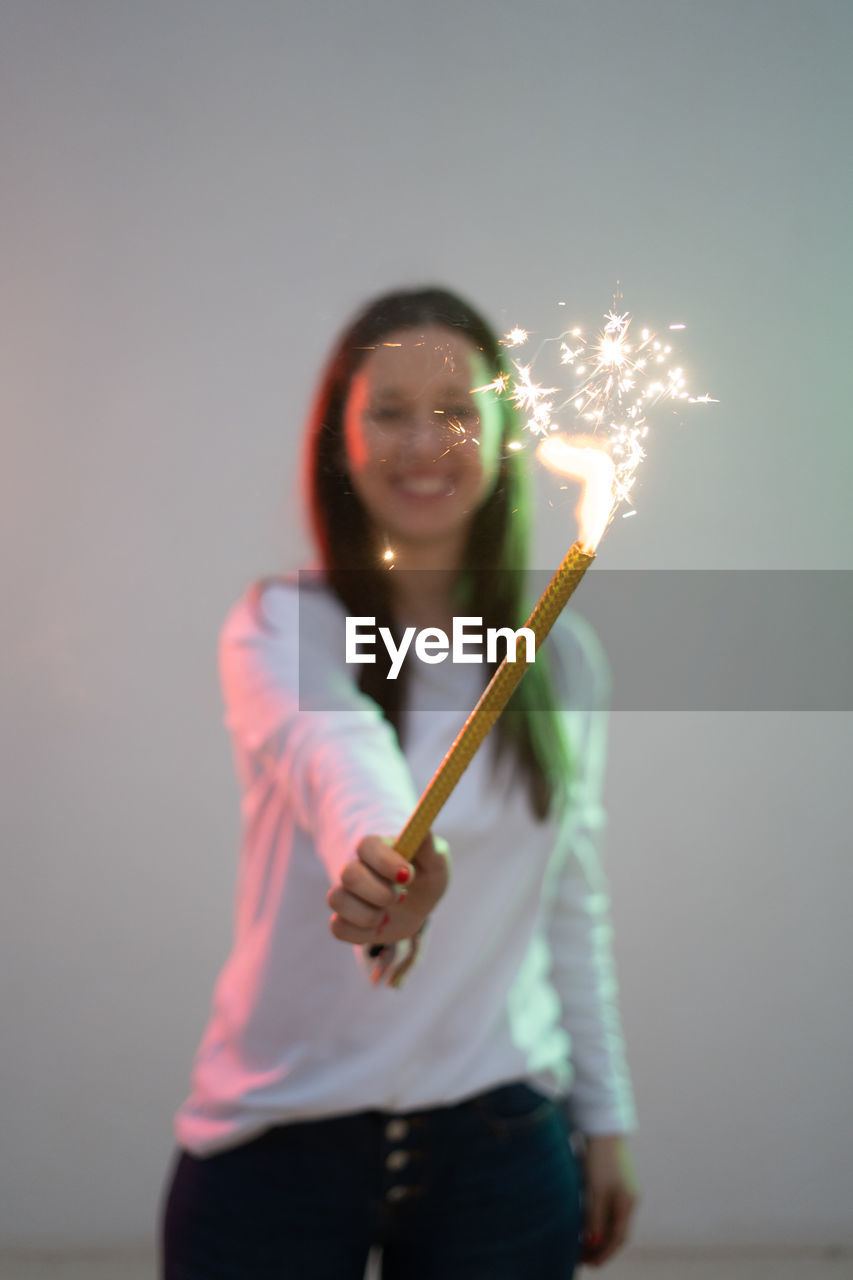 Woman holding sparkler standing against wall