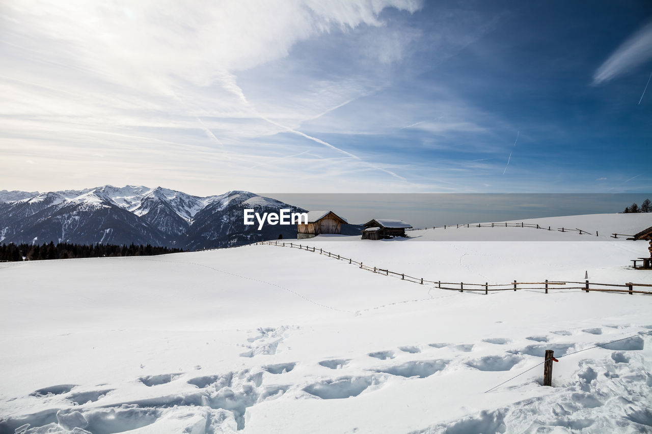 cold temperature, winter, snow, sky, mountain, beauty in nature, scenics - nature, cloud - sky, white color, nature, real people, day, covering, tranquility, mountain range, environment, tranquil scene, one person, snowcapped mountain, outdoors, extreme weather