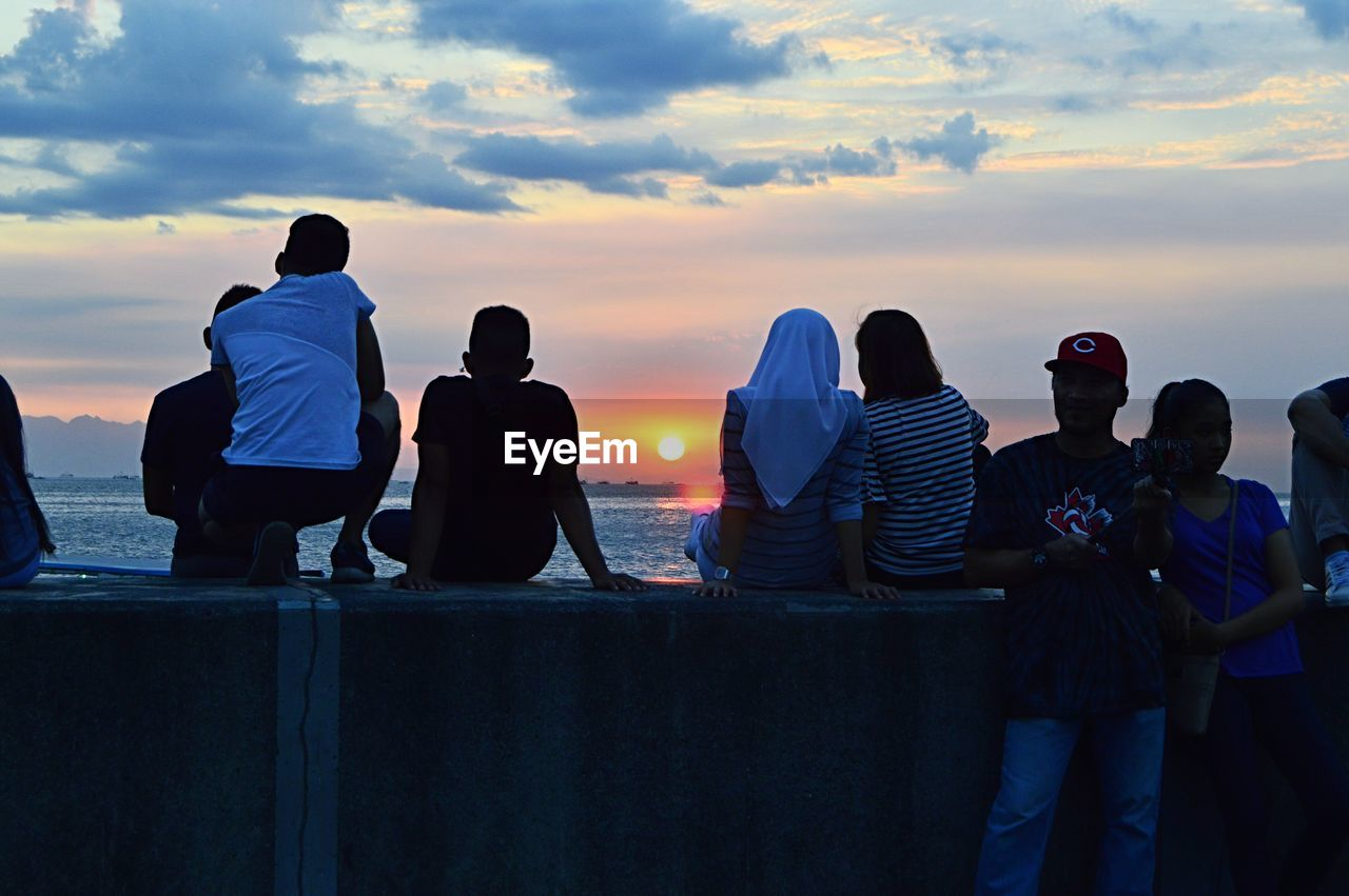 REAR VIEW OF PEOPLE SITTING ON SHORE AGAINST SKY