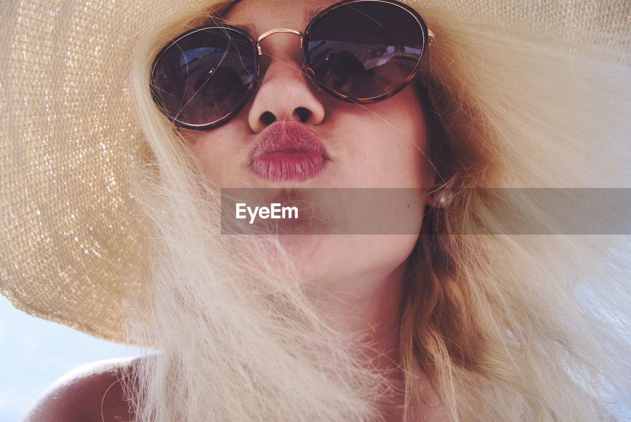 Close-up portrait of woman wearing sunglasses while puckering lips
