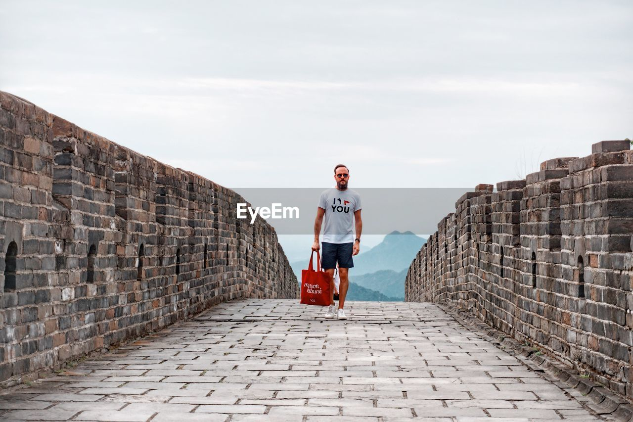full length, architecture, real people, one person, lifestyles, wall, sky, casual clothing, built structure, leisure activity, day, standing, wall - building feature, cloud - sky, adult, direction, front view, footpath, building exterior, outdoors, stone wall, paving stone