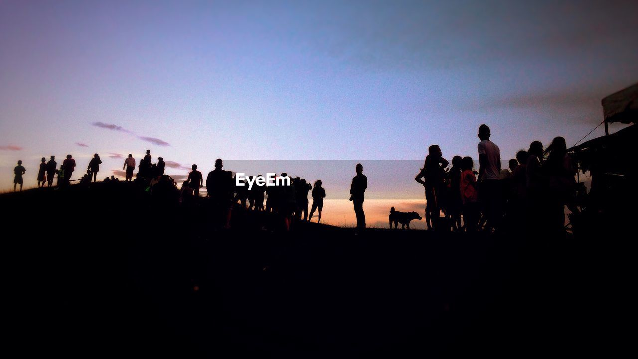 large group of people, real people, men, clear sky, leisure activity, silhouette, women, sky, togetherness, lifestyles, outdoors, sunset, photographing, day, nature, adult, people