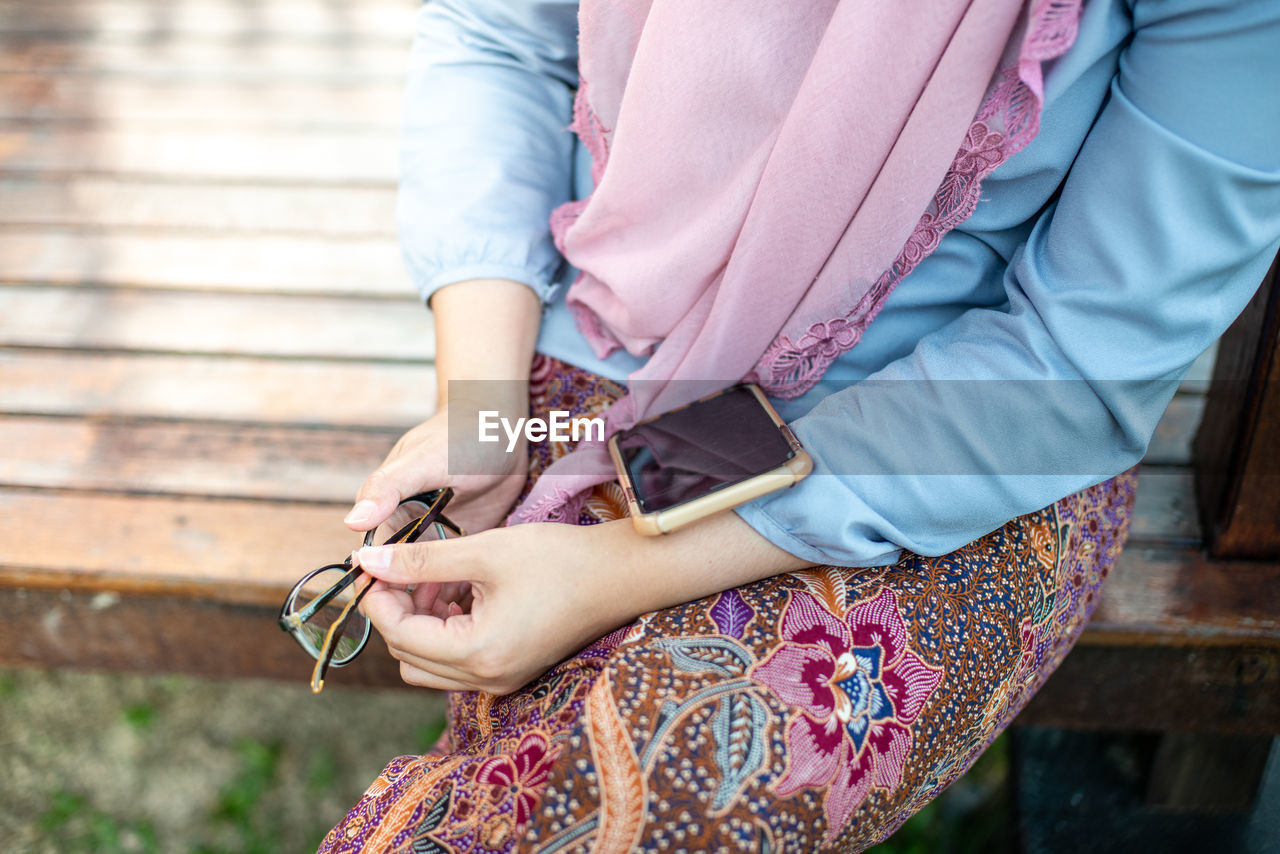 Midsection of woman wearing hijab with smart phone outdoors
