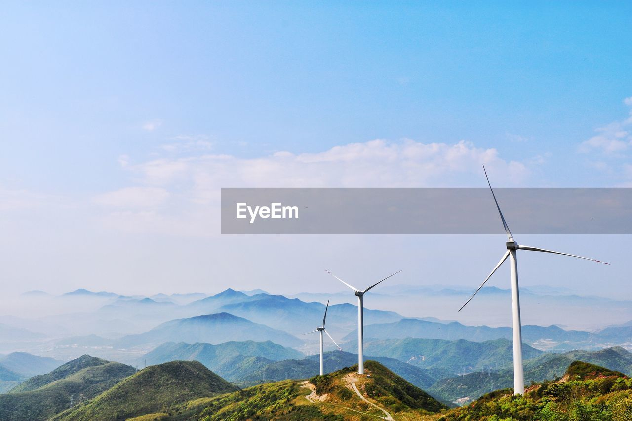 Wind Turbines In Mountains Against Blue Sky