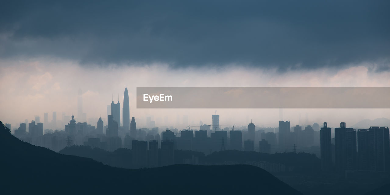 Silhouette skyscrapers in city against sky during foggy weather