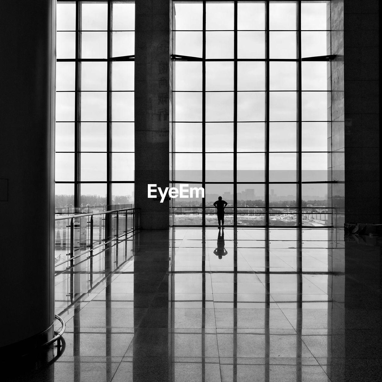 Man Looking Through Window Against Sky