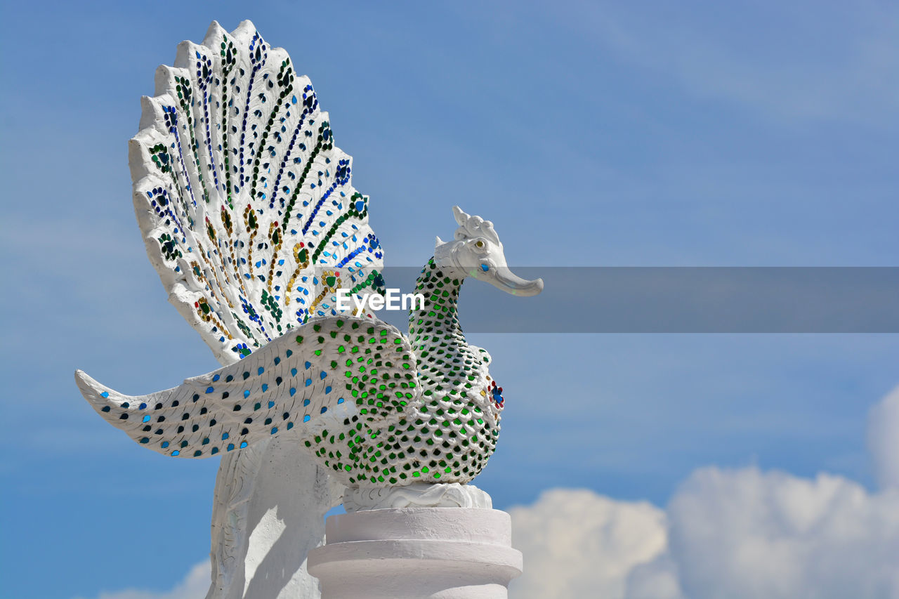 sky, animal themes, nature, representation, animal, day, sculpture, low angle view, cloud - sky, animal representation, art and craft, no people, focus on foreground, statue, one animal, creativity, sunlight, vertebrate, outdoors, blue