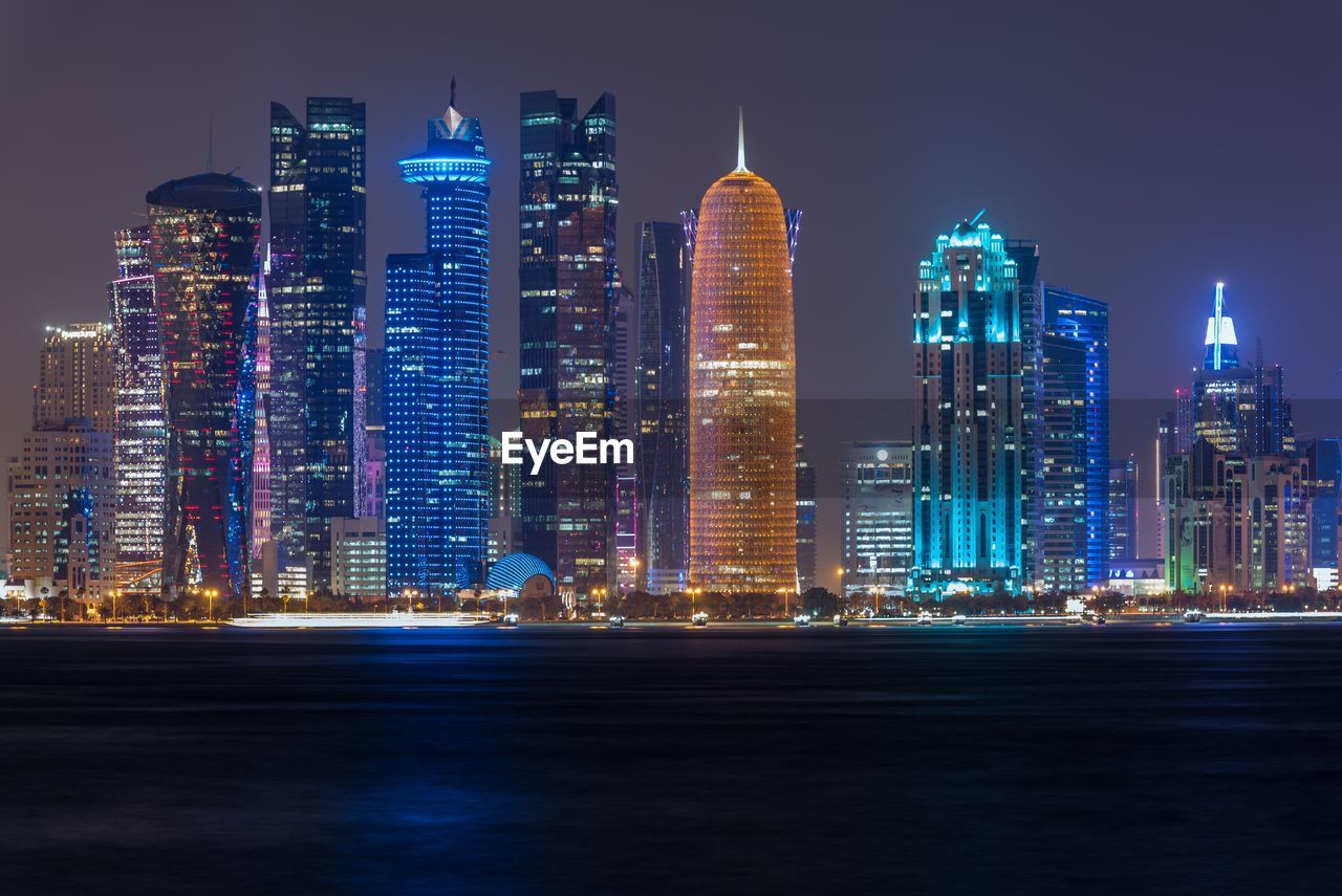 architecture, skyscraper, illuminated, night, building exterior, city, built structure, cityscape, modern, travel destinations, tower, urban skyline, downtown district, waterfront, no people, outdoors, water, sky