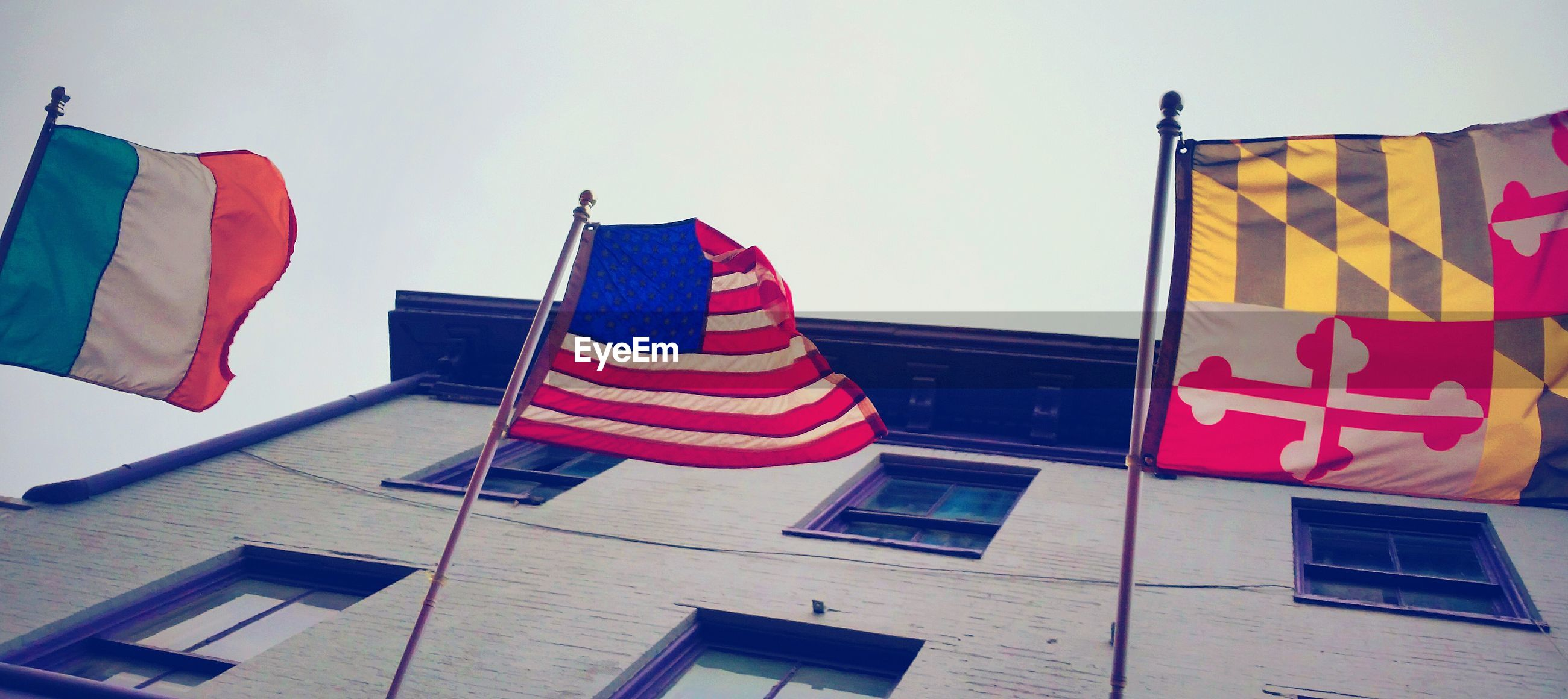 LOW ANGLE VIEW OF FLAG AGAINST BUILDING