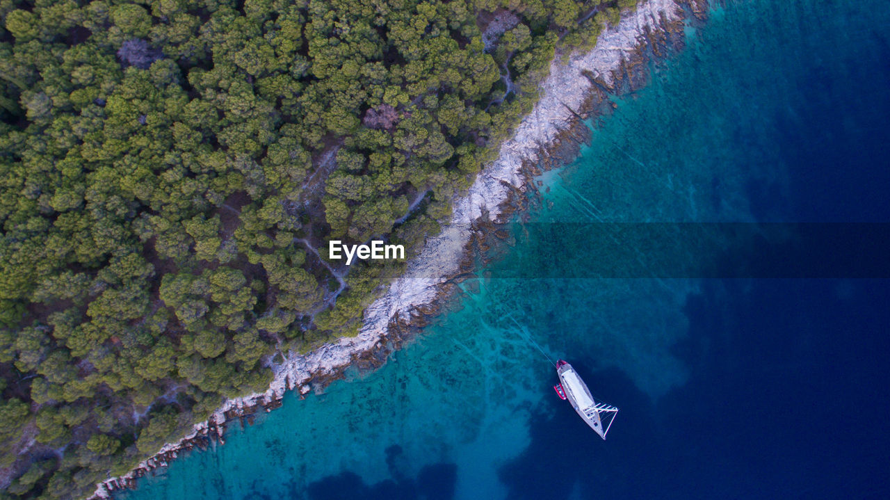 Aerial View Of Boat Moored In Sea By Forest