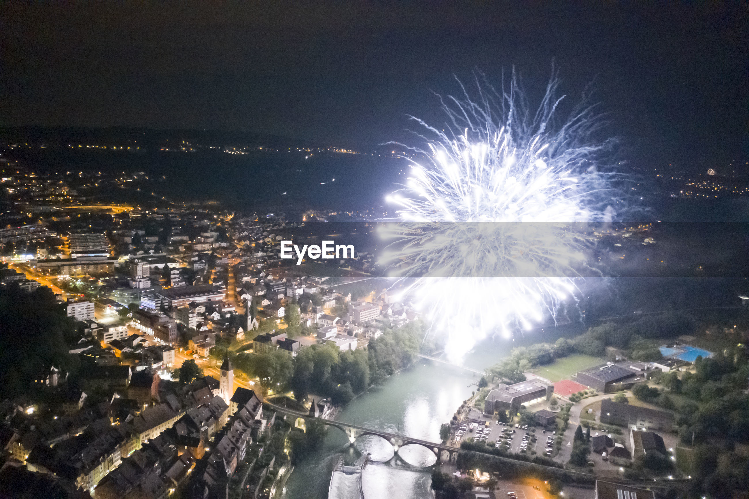HIGH ANGLE VIEW OF FIREWORK DISPLAY AT NIGHT