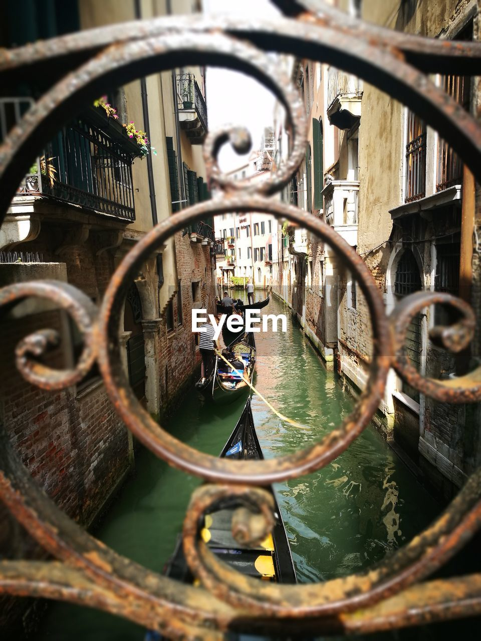 Man Standing On Gondola Sailing On Canal Amidst Buildings Seen Through Wrought Iron