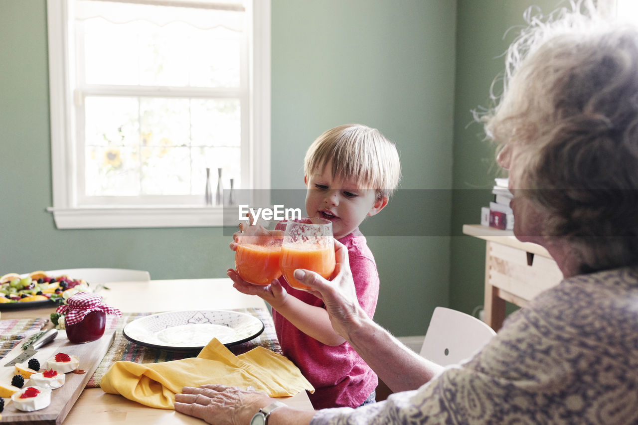 food and drink, childhood, child, lifestyles, food, men, boys, males, indoors, freshness, sitting, table, casual clothing, domestic life, togetherness, real people, drink, women, breakfast