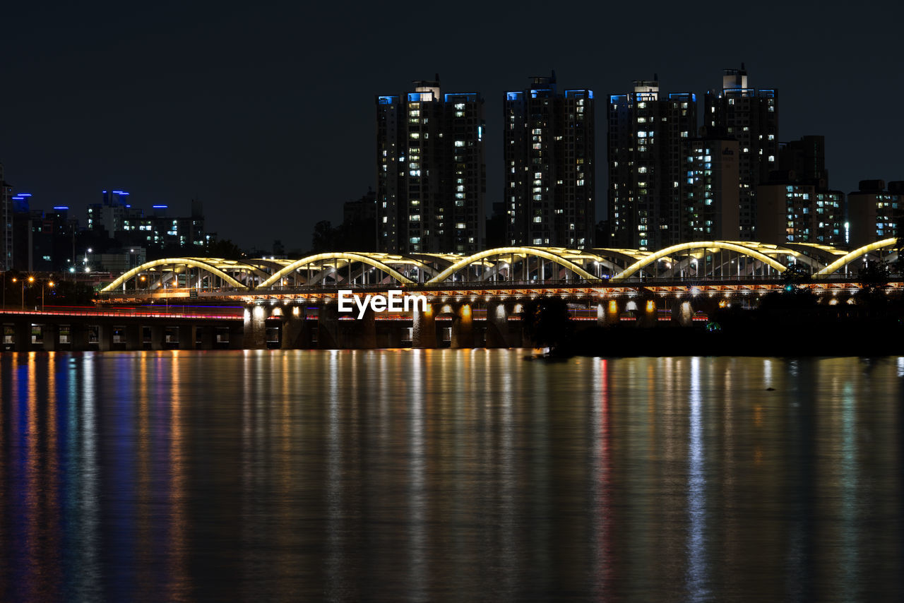 night, illuminated, architecture, built structure, bridge - man made structure, building exterior, connection, city, skyscraper, transportation, no people, cityscape, travel destinations, outdoors, water, modern, sky