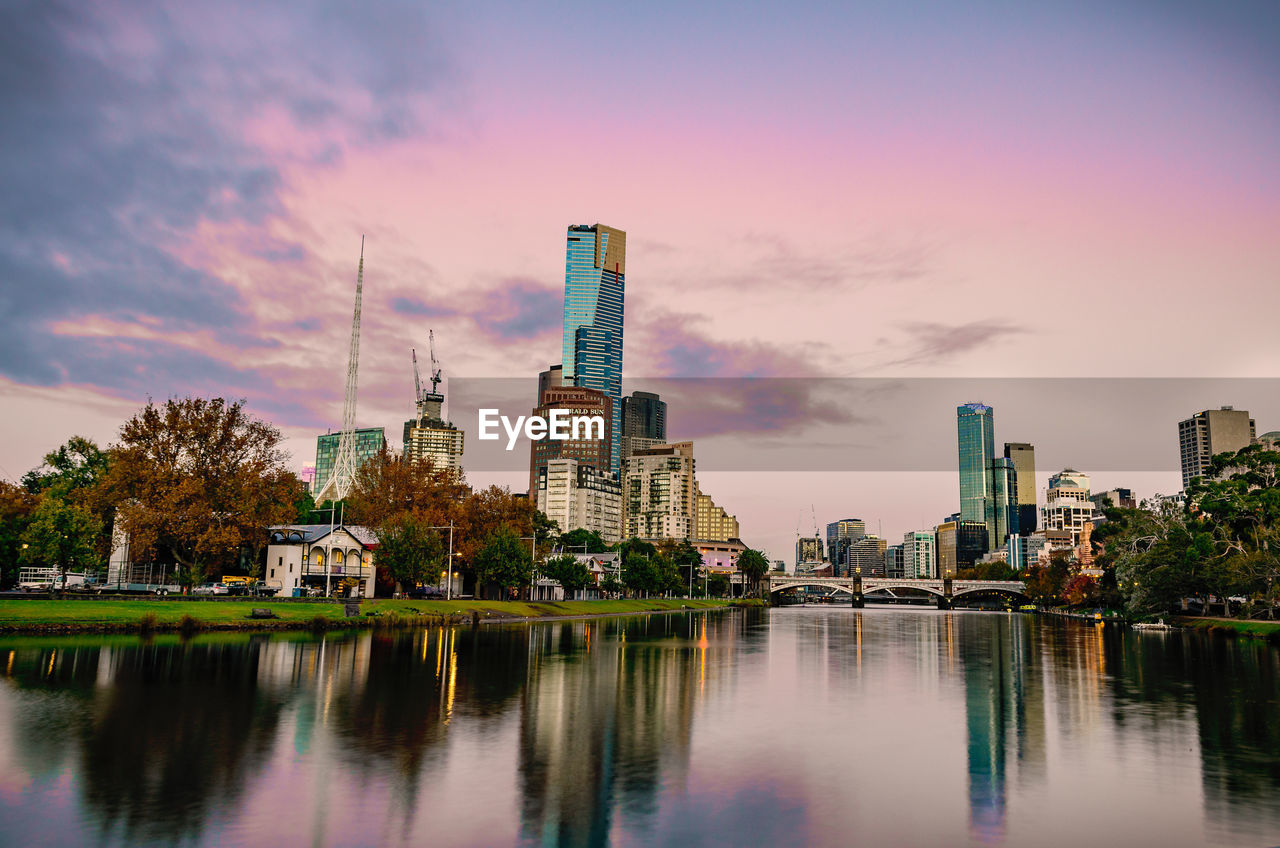 building exterior, built structure, architecture, water, sky, building, city, waterfront, reflection, sunset, tall - high, river, no people, cloud - sky, tower, office building exterior, nature, residential district, skyscraper, outdoors, modern, cityscape, financial district, spire