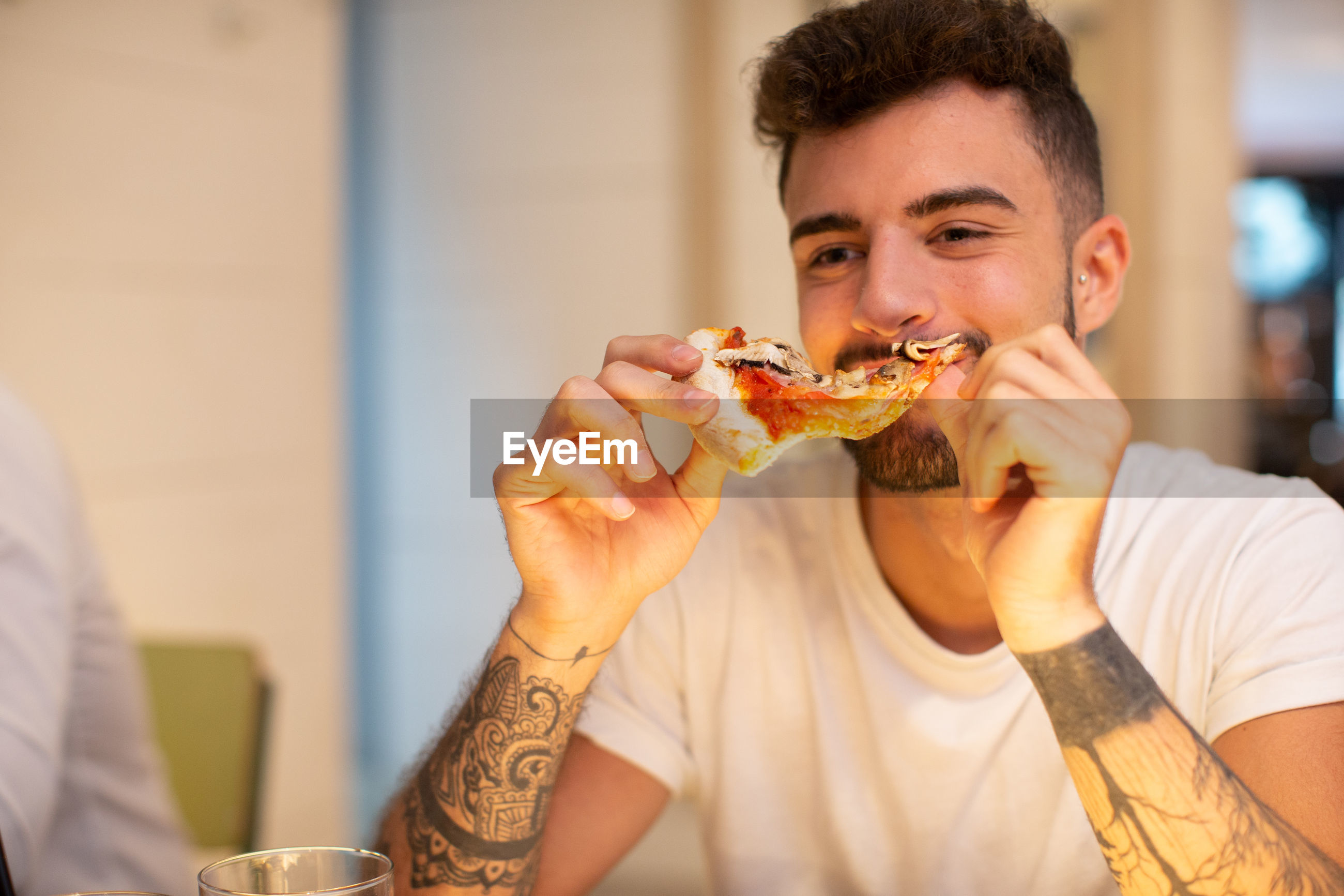 Young man eating pizza indoors