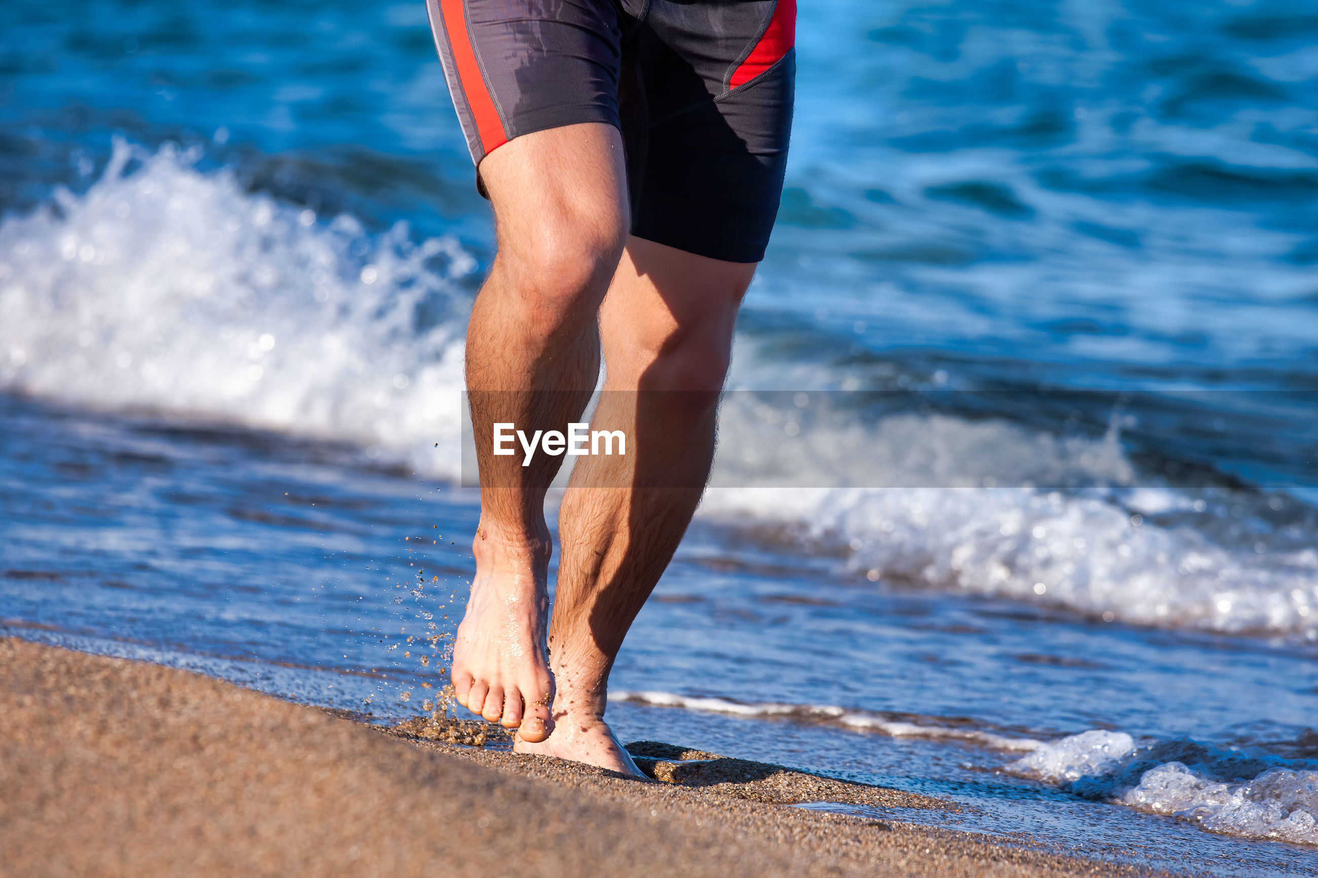 Low section of man running on beach