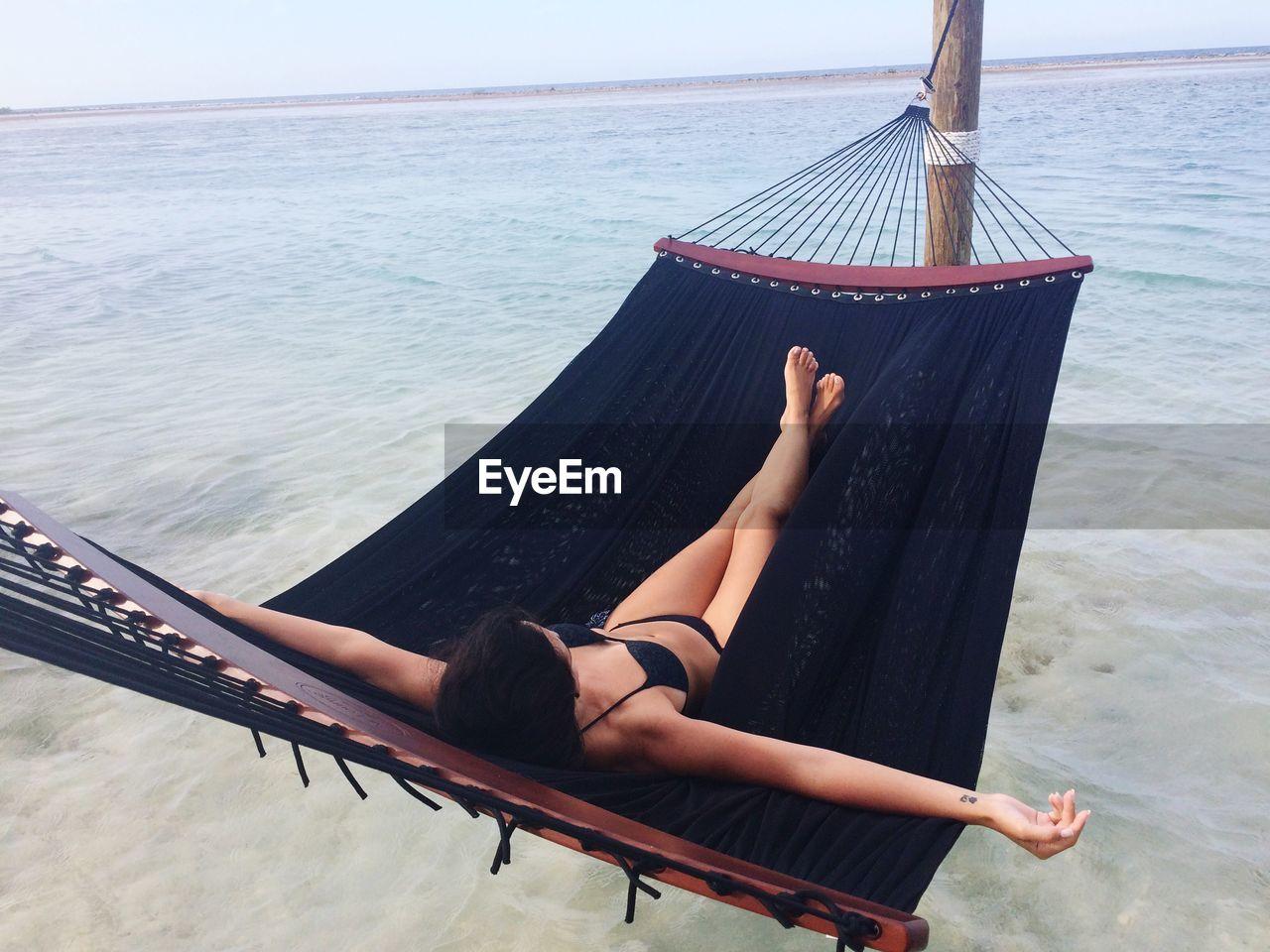 Full length of woman relaxing in hammock at sea