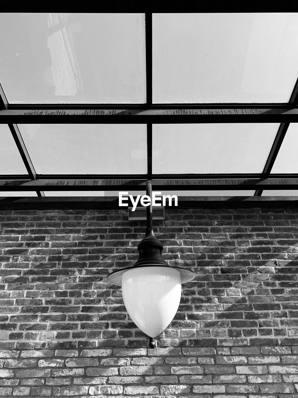 lighting equipment, brick wall, low angle view, wall - building feature, brick, hanging, wall, no people, built structure, architecture, illuminated, electric lamp, electric light, indoors, electricity, ceiling, day, light, light bulb, light fixture