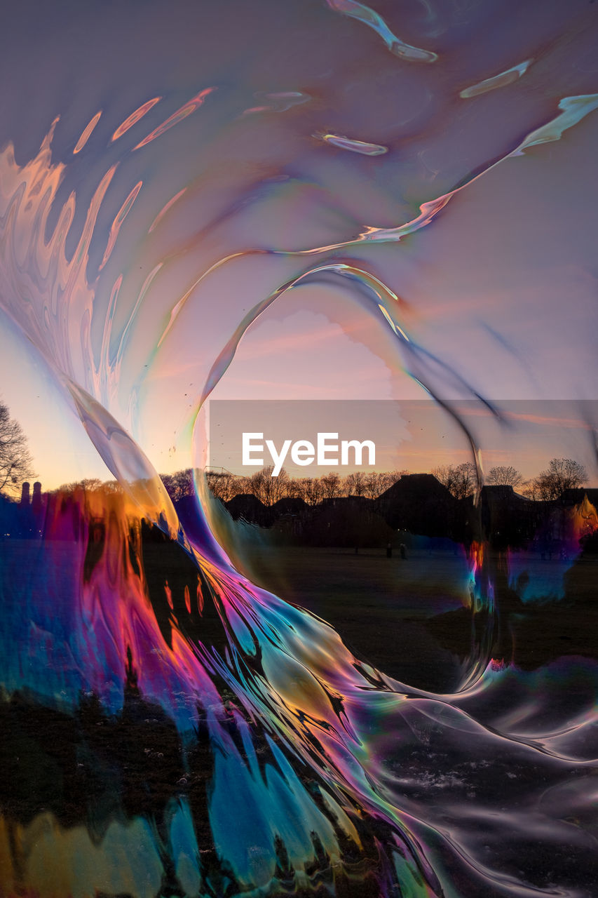 DIGITAL COMPOSITE IMAGE OF RAINBOW AGAINST SKY DURING SUNSET