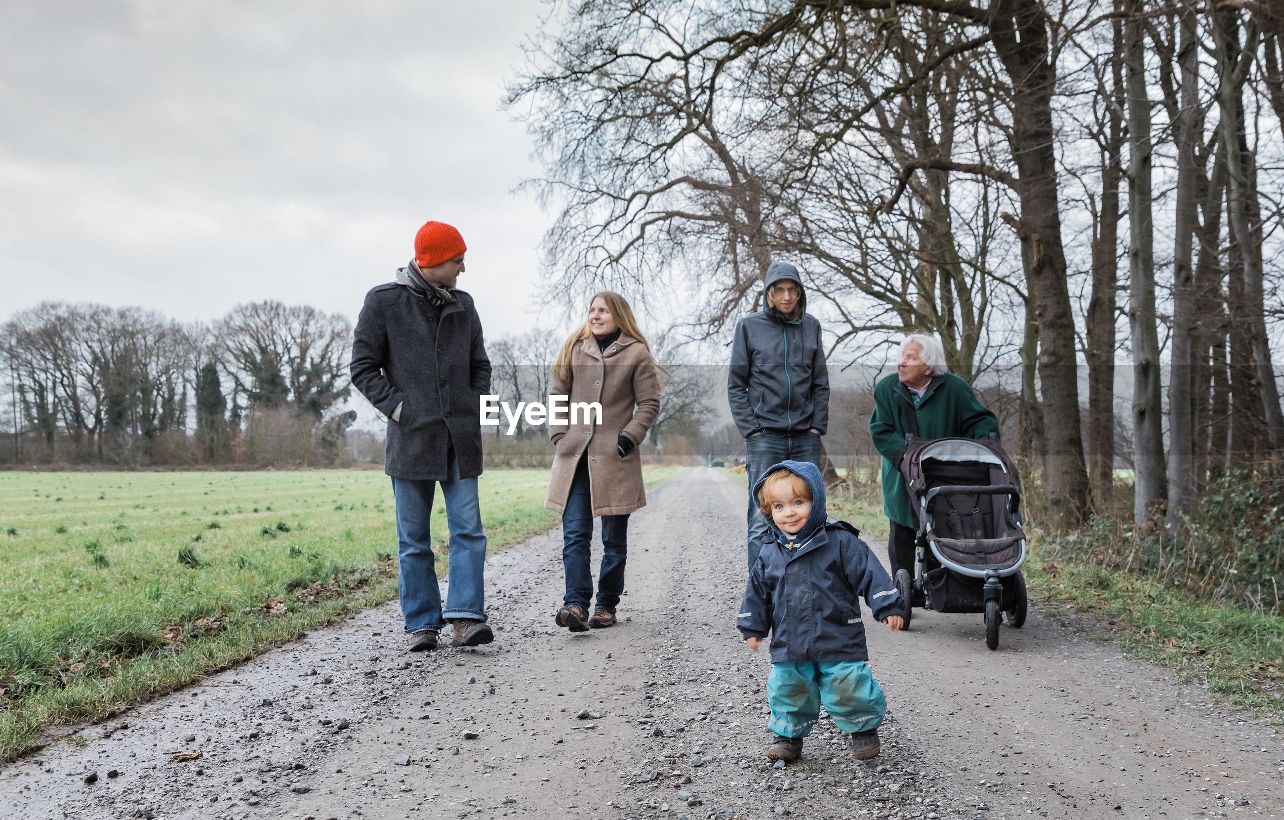 Full length of family walking on road during winter