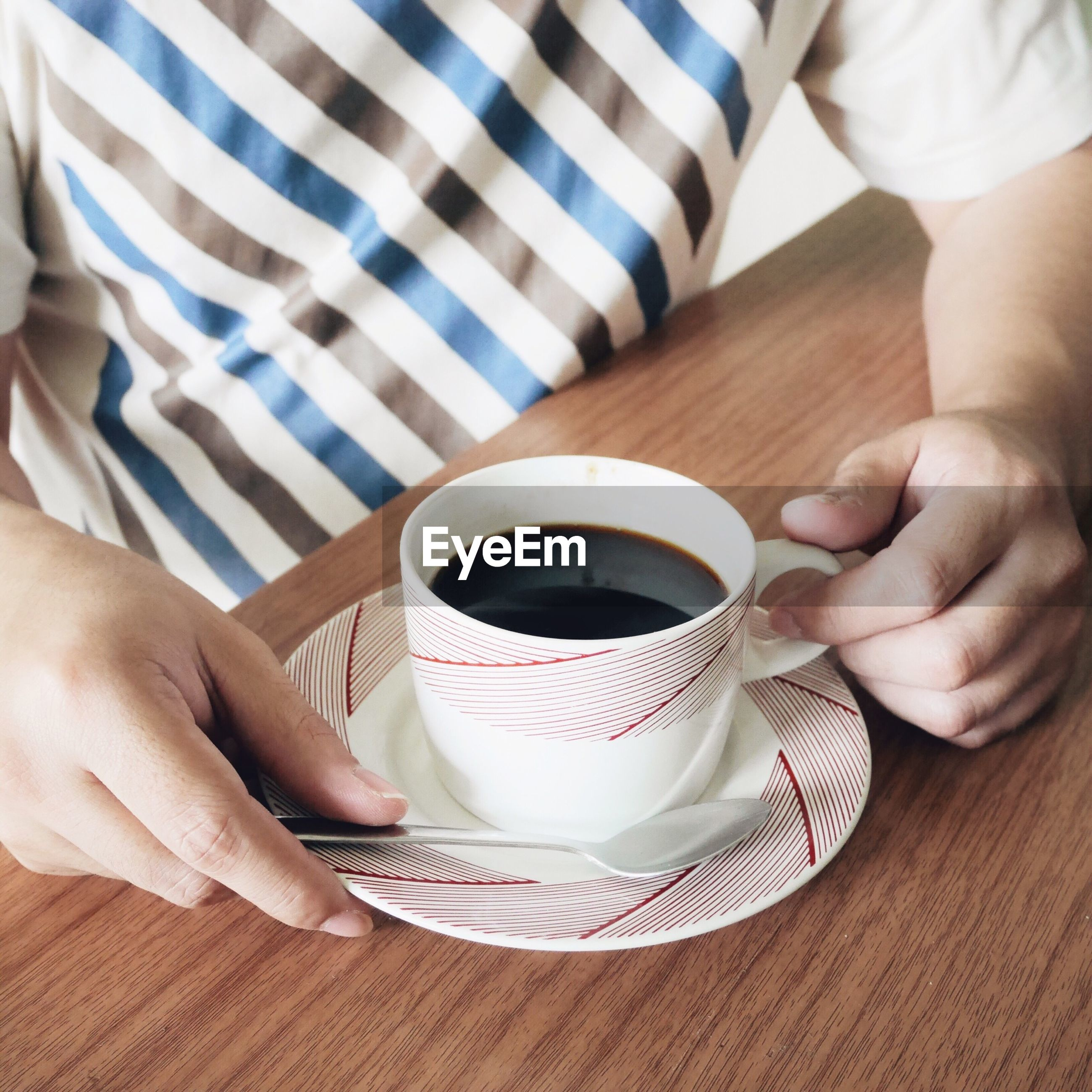 Midsection of man with black coffee at table