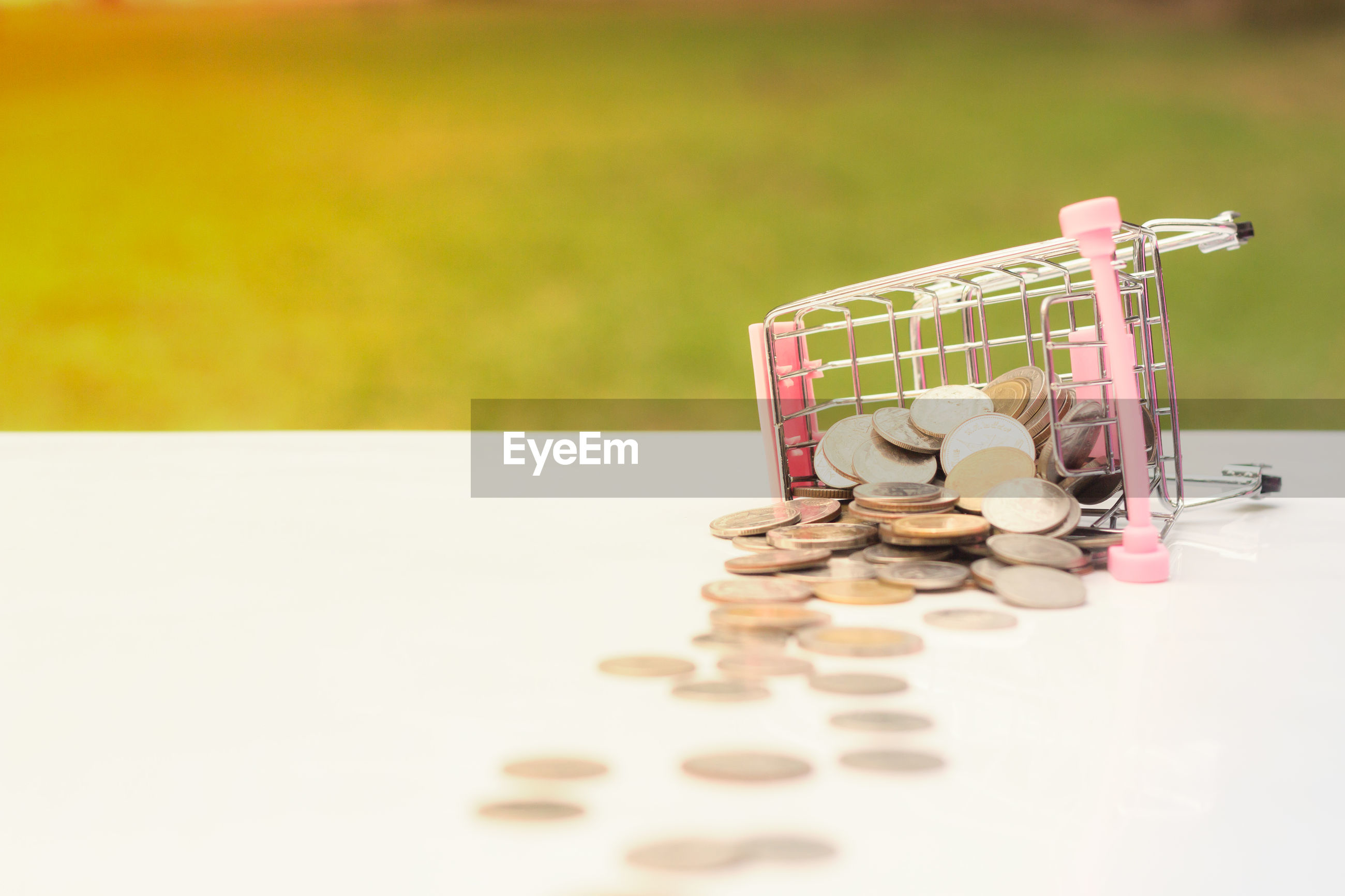 Close-up of small shopping cart and coins on table