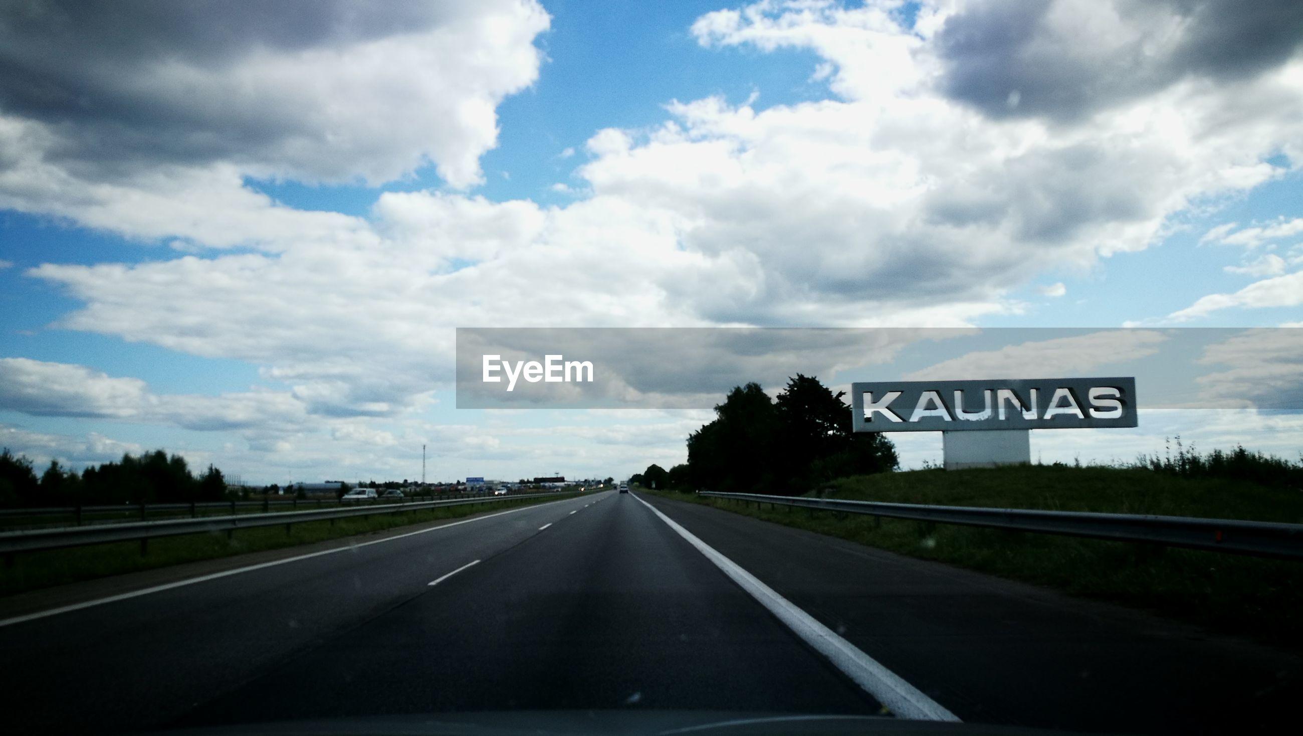 Road against cloudy sky seen through car windshield