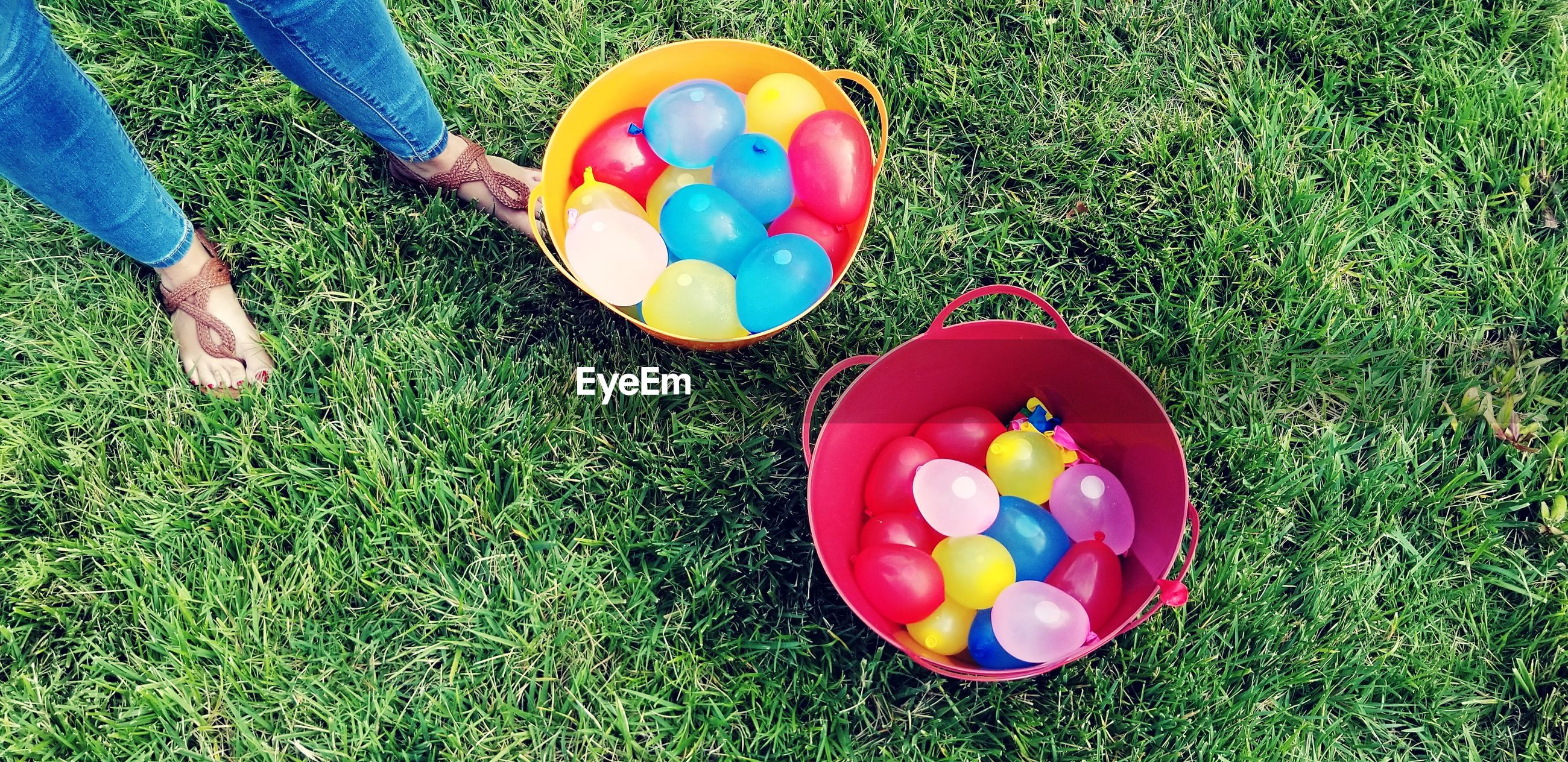 multi colored, grass, easter, easter egg, one person, high angle view, easter egg hunt, day, outdoors, human body part, celebration, childhood, low section, balloon, real people, human hand, people