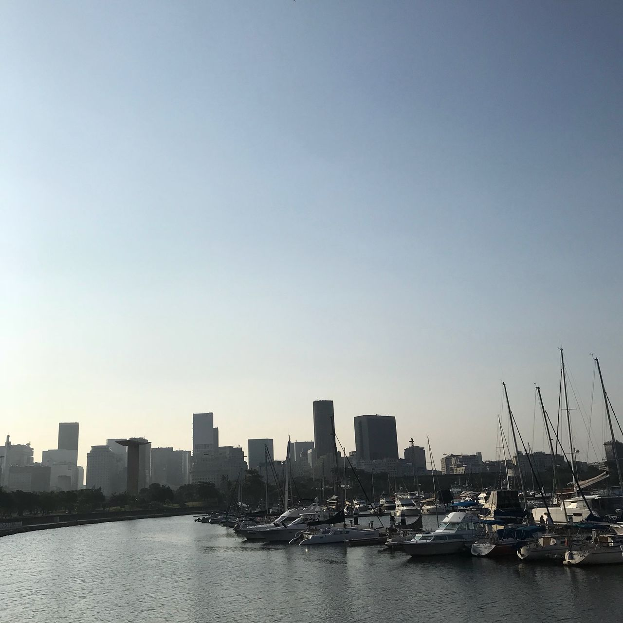 water, sky, architecture, building exterior, city, built structure, building, transportation, no people, clear sky, waterfront, copy space, nature, sea, nautical vessel, landscape, mode of transportation, urban skyline, outdoors, cityscape, office building exterior, skyscraper, sailboat, marina