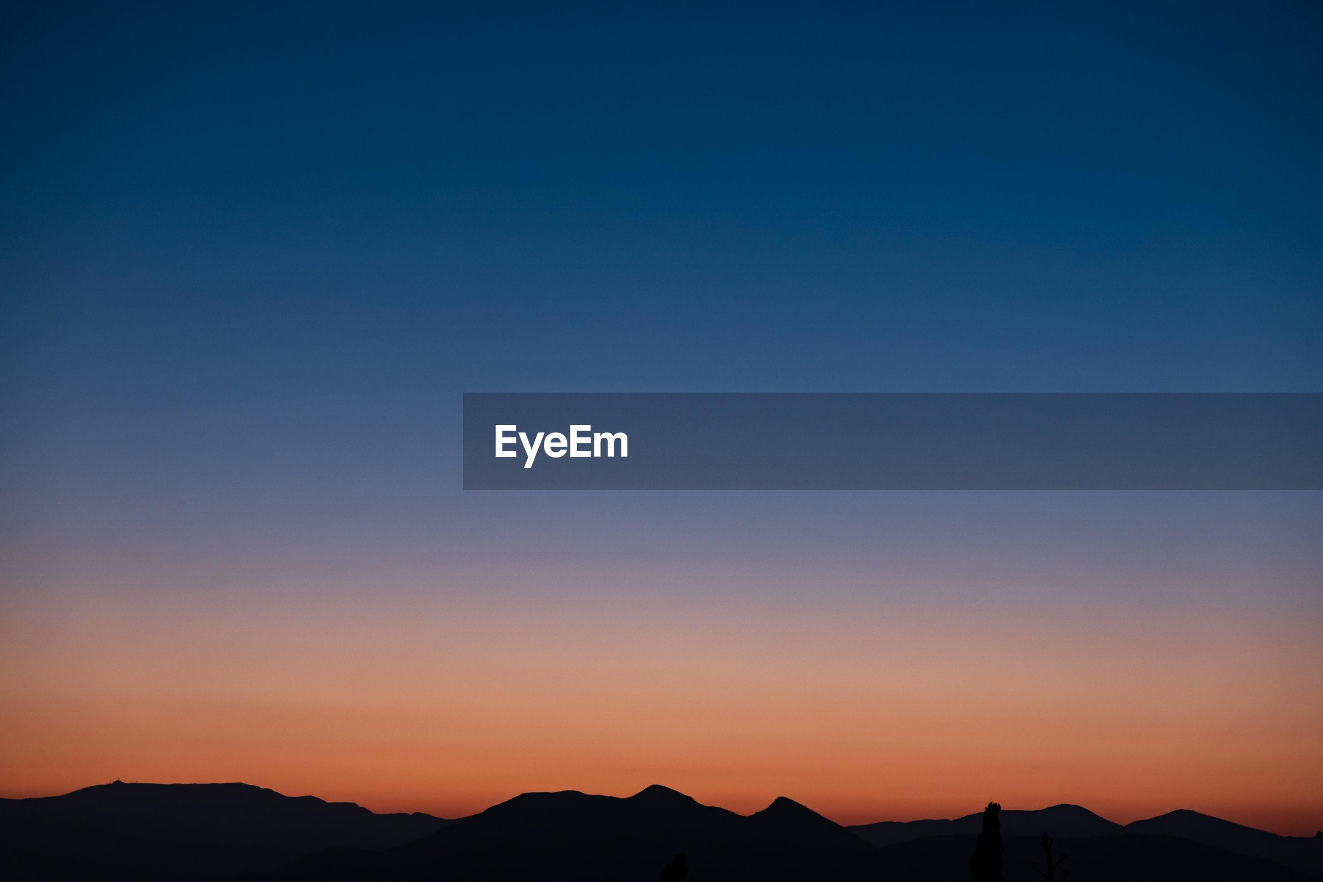 SILHOUETTE MOUNTAIN AGAINST CLEAR SKY AT SUNSET