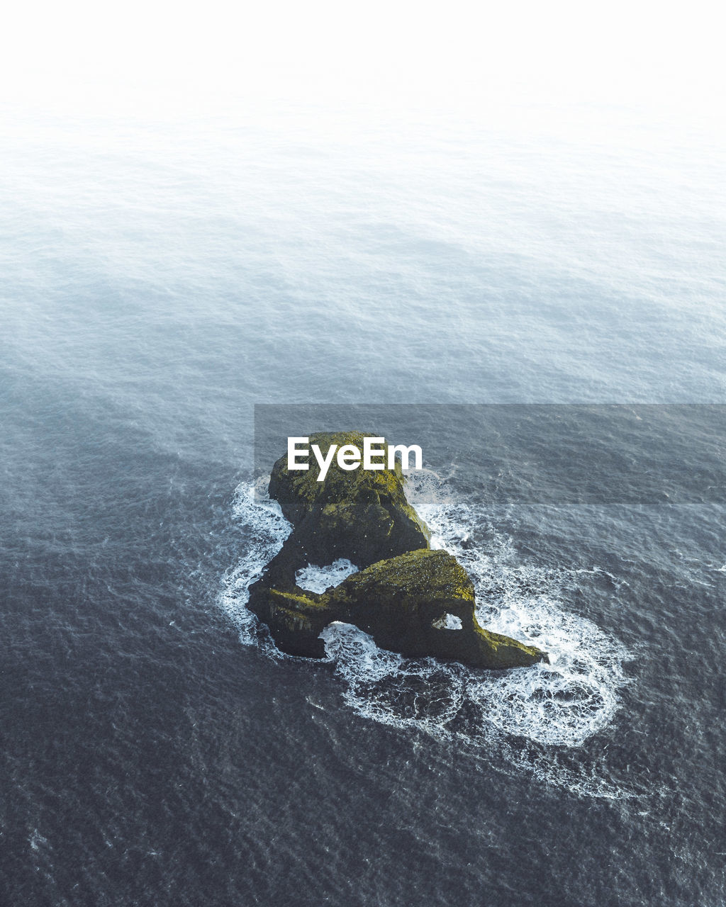 Aerial view of rock formation amidst sea