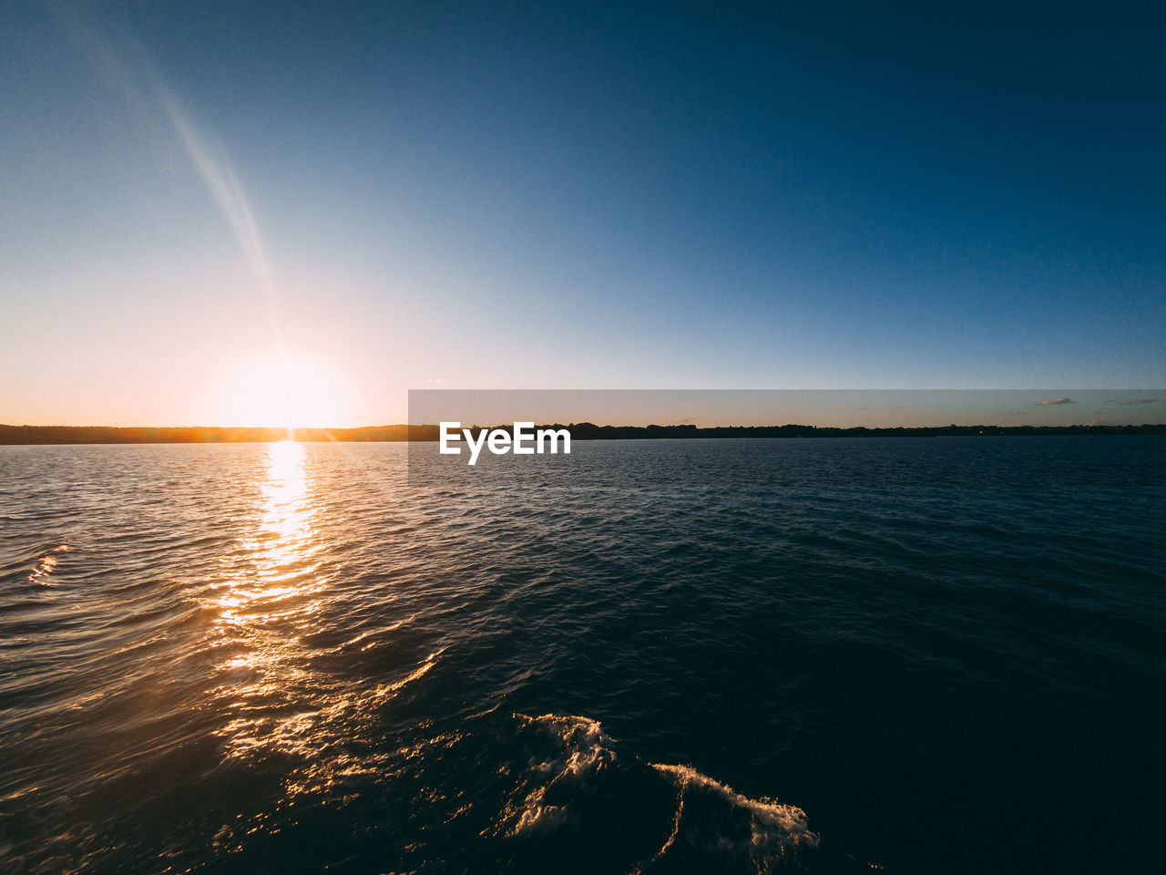 sky, water, beauty in nature, sea, scenics - nature, tranquility, tranquil scene, sunset, nature, sunlight, idyllic, no people, sun, waterfront, horizon, non-urban scene, copy space, clear sky, outdoors, horizon over water