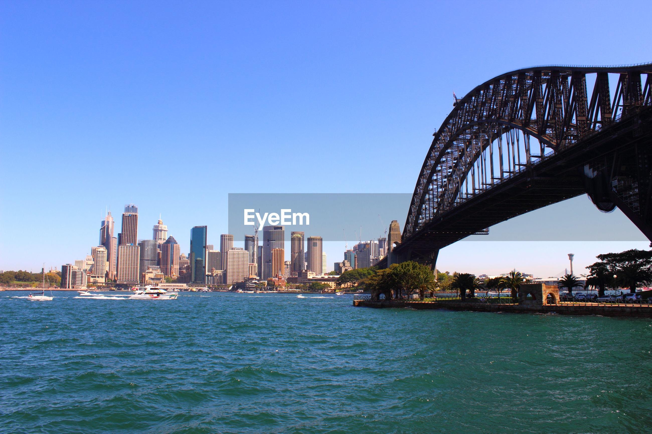SEA BY CITY BUILDINGS AGAINST CLEAR SKY