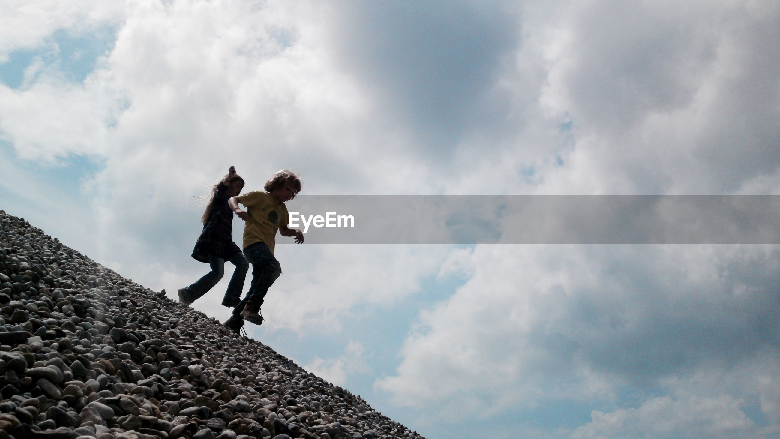 Siblings walking on heap of stones at construction site against cloudy sky