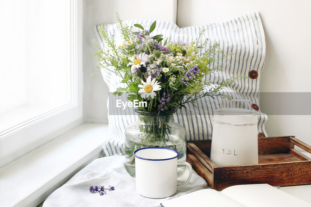 flower, flowering plant, plant, table, indoors, white color, vase, nature, freshness, no people, window, container, beauty in nature, fragility, vulnerability, home interior, flower arrangement, flower head, day, cup, bunch of flowers, bouquet, glass, purple