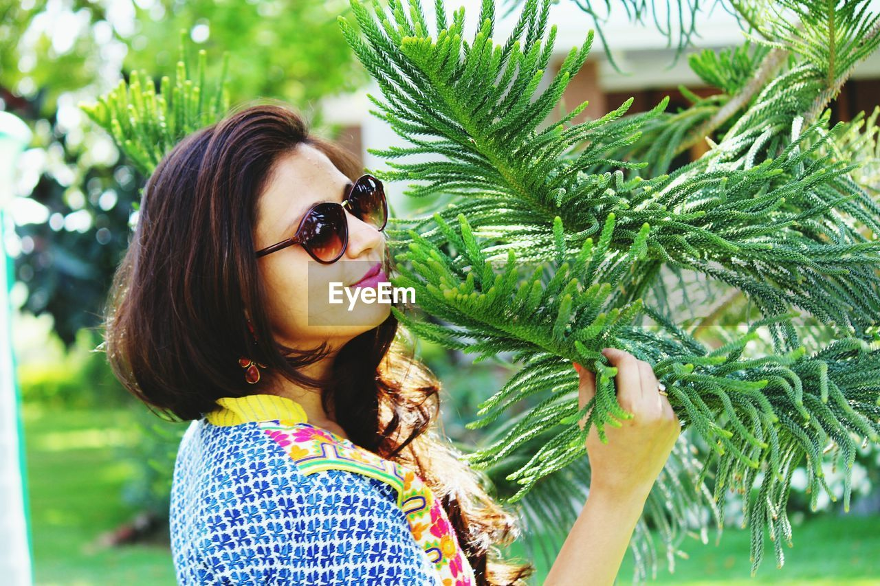 Woman standing by pine tree at park
