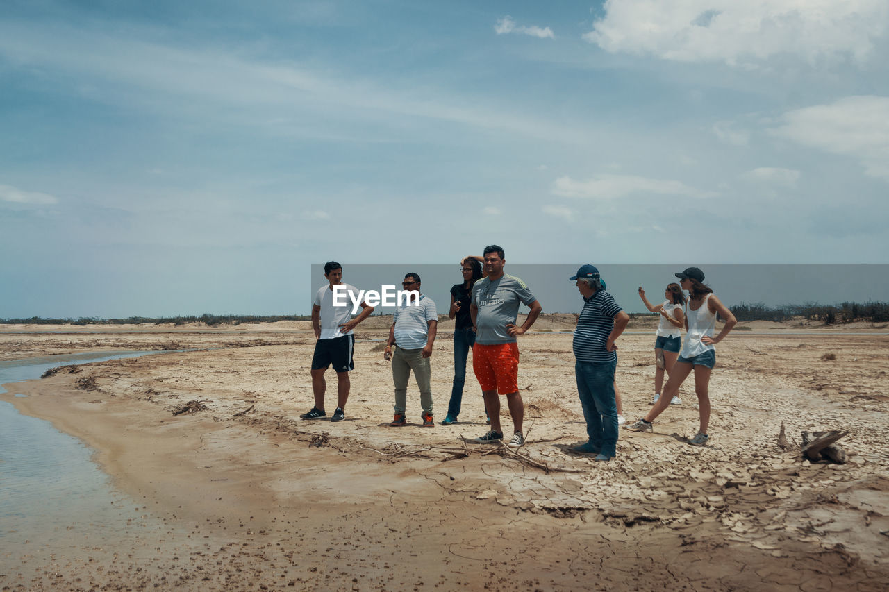 sky, men, land, group of people, real people, standing, cloud - sky, full length, beach, medium group of people, nature, group, day, leisure activity, lifestyles, adult, people, togetherness, casual clothing, women