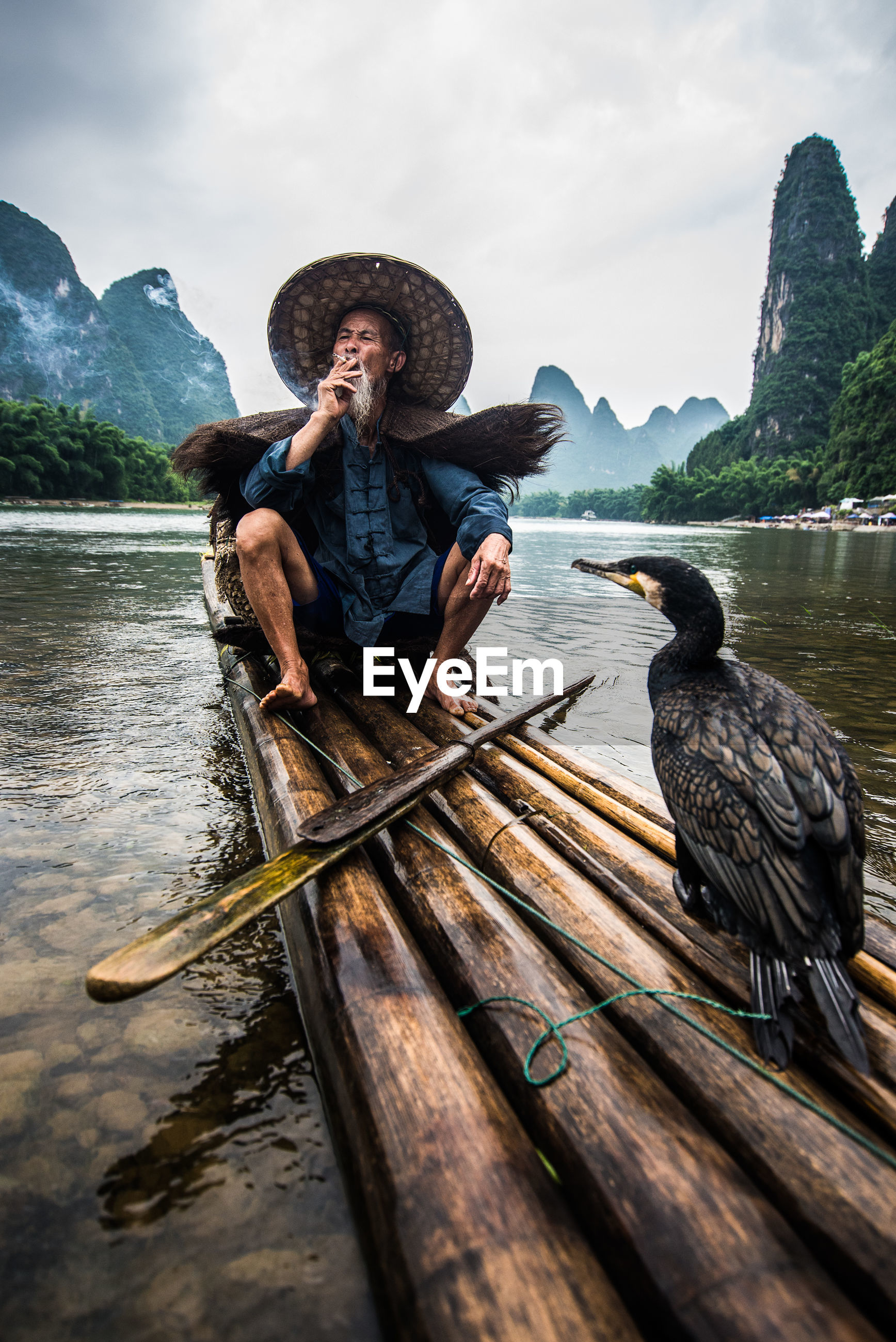 Full length of fisherman with cormorant on wooden raft in river against sky