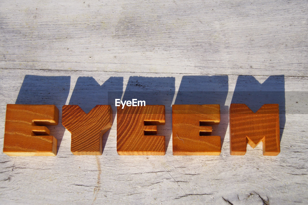 High Angle View Of Eyeem Text On Table During Sunny Day