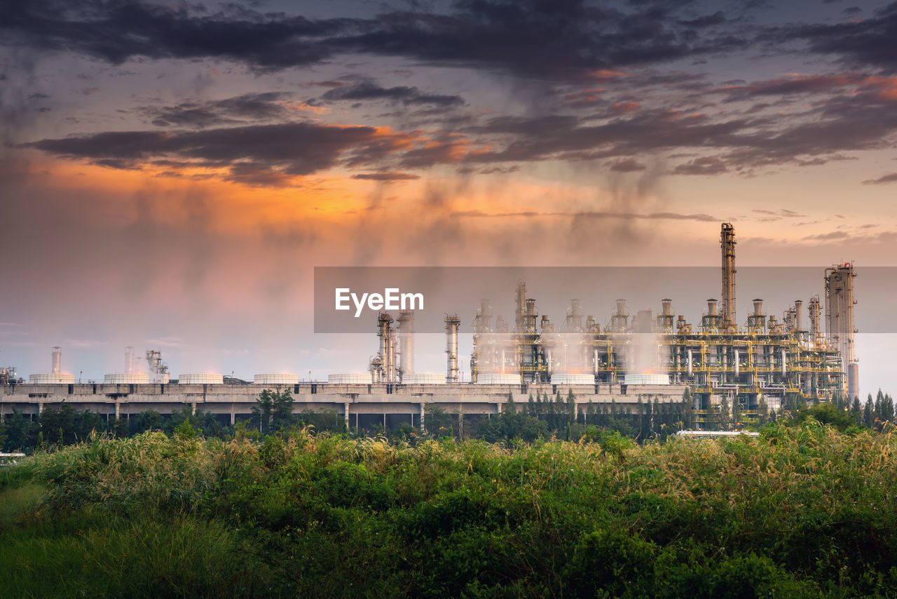 cloud - sky, building exterior, sky, factory, built structure, industry, sunset, architecture, plant, fuel and power generation, nature, smoke stack, no people, tree, environment, environmental issues, outdoors, pollution, industrial building, growth, air pollution