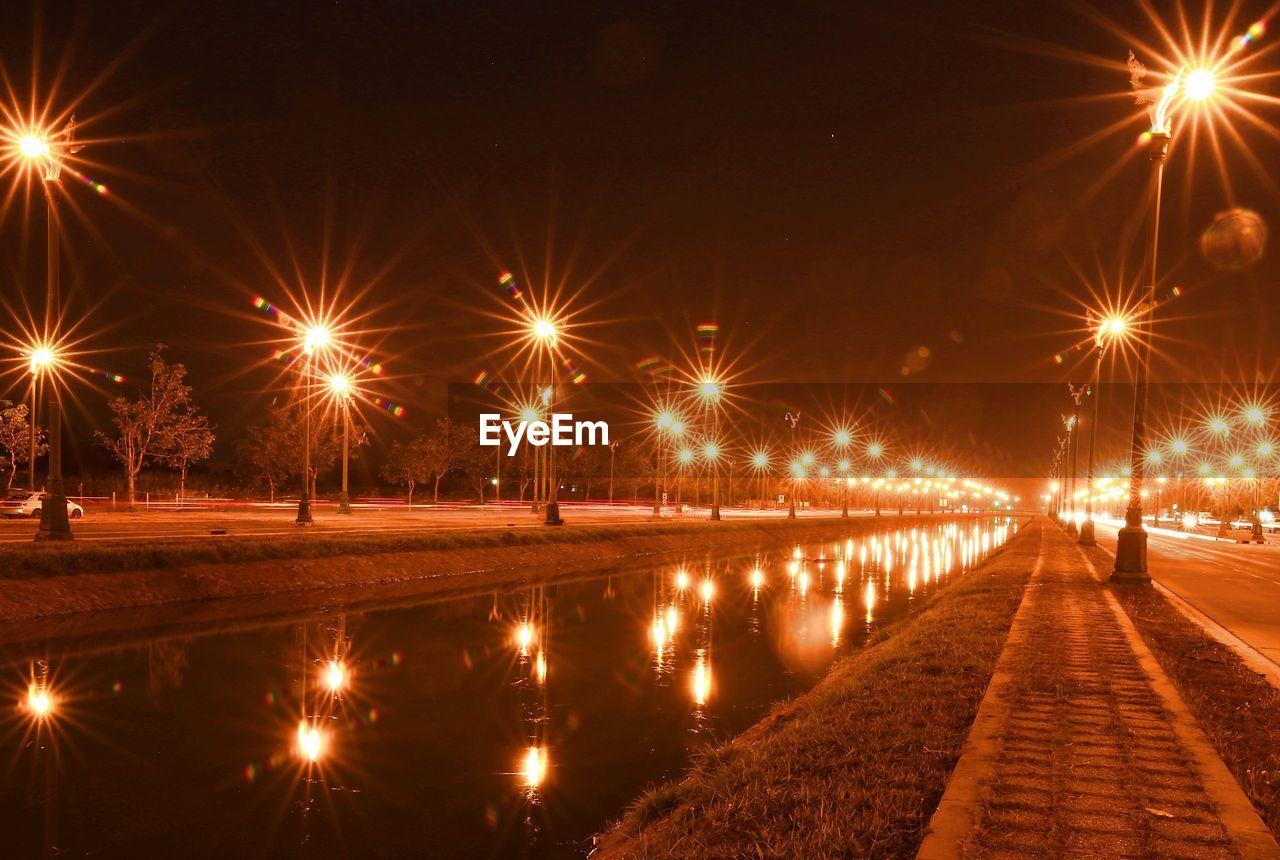Illuminated street lights by river at night