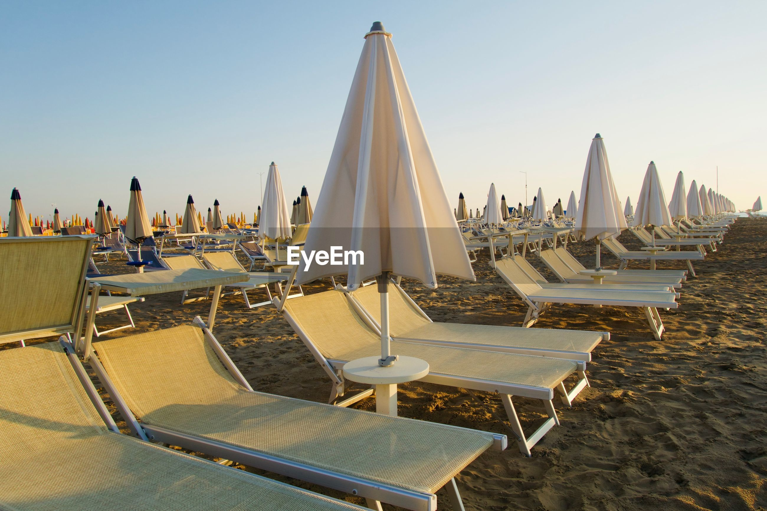 Panoramic view of lounge chairs and umbrellas on beach against clear sky